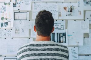 Emprendedor joven mira un panel con ideas de negocio.